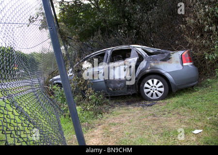 burned out stolen car crashed into a chain link fence in the uk - Stock Photo