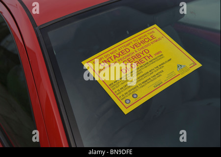 Warning sticker on the window of a car with no road tax clamped by the DVLA, UK - Stock Photo