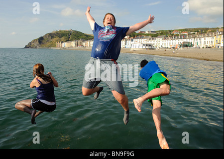 Three Teenagers jumping into the sea off the jetty on the beach at Aberystwyth Wales UK on a hot day in summer, - Stock Photo