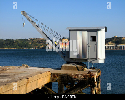 An old Quayside crane on the waterfront of the River Tagus in Lisbon Portugal - Stock Photo