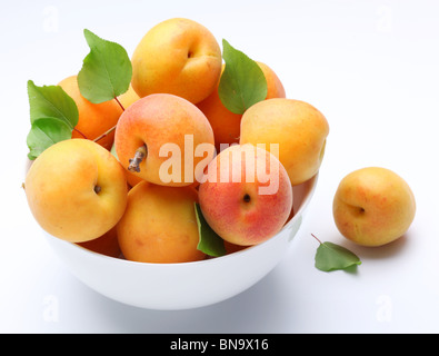 Crockery with mellow apricots. Isolated on a white background. - Stock Photo
