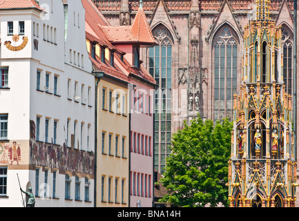 Schoner Brunnen fountain together with shop facades and church. Seen from Hauptmarkt in Nuremburg, Germany - Stock Photo