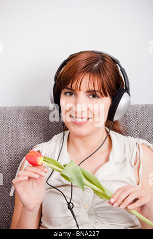 Beautiful woman listening music and holding a orange tulip on the hands - Stock Photo
