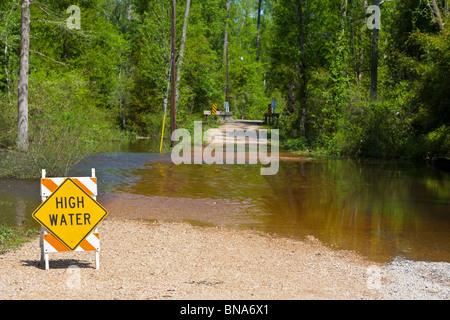 Abita Springs, LA - Mar 2009 - Sign warns of high water on flooded roads in rural Abita Springs, Louisiana - Stock Photo