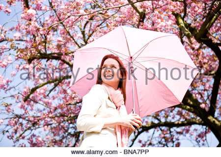 A young woman holding an umbrella, in springtime - Stock Photo