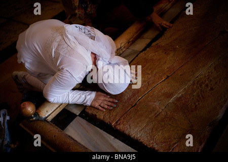 A Christian pilgrims kneels in prayer over the Stone of the Anointing or Stone of Unction inside the church of Holy - Stock Photo