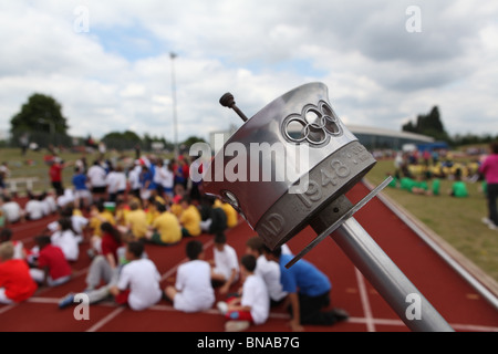 the olympic torch from 1941 being held at an event to promote the 2012 olympics being held in london there are crowds - Stock Photo