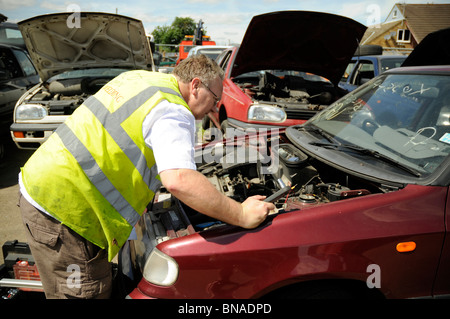 Man wearing hi-vis vest inspecting engine in a car in breakers yard. - Stock Photo