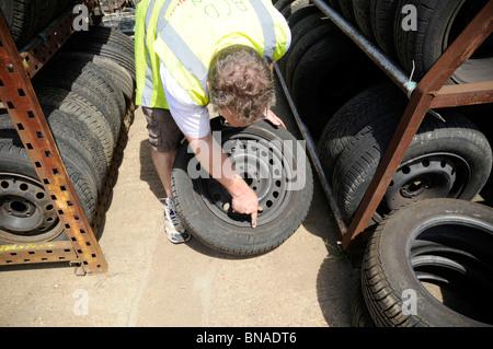 Man wearing hi-vis vest inspecting wheel and tyre in a car breakers yard. - Stock Photo
