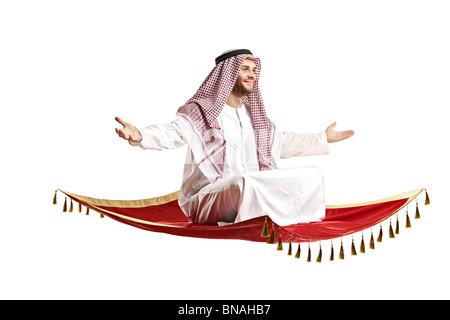 An Arab person sitting on a flying carpet - Stock Photo