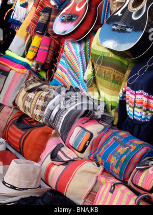 Colourful handicrafts includung bags, hats and guitars on sale on a market stall in Uyuni in Bolivia - Stock Photo