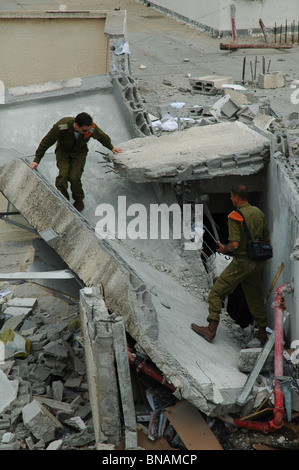 Israeli officers from the Search and Rescue Brigade surveys the damage in a residential building caused by a Hezbollah - Stock Photo