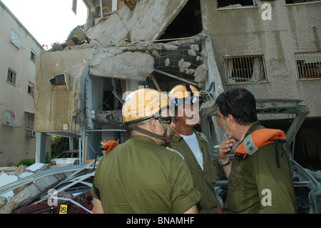 Israeli officers from the Search and Rescue Brigade stand amid the rubble of a destroyed residential building after - Stock Photo