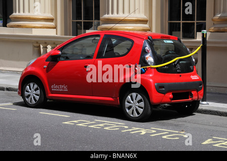 Electric car charging via public charging station on pavement mounted bollard beside marked out designated parking - Stock Photo