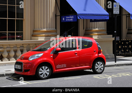 Electric car parked in designated bay for electric vehicles cabled to public charging station on pavement facility - Stock Photo