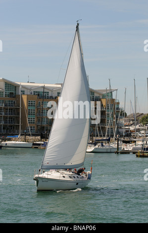 Sailing in Portsmouth Harbour with a backdrop of Gosport and a modern waterfront property development southern Hampshire - Stock Photo
