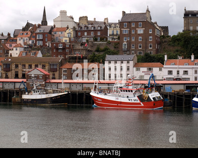 Two fishing boats one modern and the other old at Whitby fish quay North Yorkshire - Stock Photo