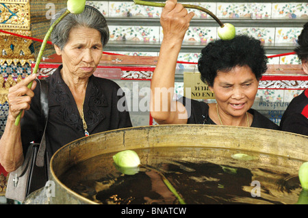 Women, dressed in black, because of the death of the Kings sister,  pray at a shrine within The Grand Palace Bangkok - Stock Photo