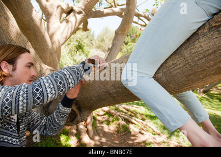 Young man carving tree that woman is sitting on