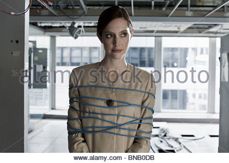 Businesswoman tied up in cables - Stock Photo