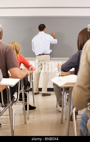 High school teacher using white board in classroom - Stock Photo