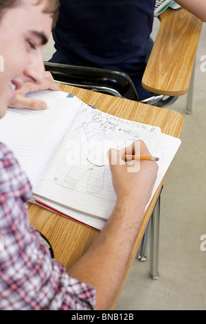 Male high school student doodling in notebook - Stock Photo