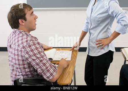 Male high school student being told off for doodling - Stock Photo