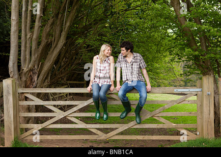 Young couple sitting on gate - Stock Photo