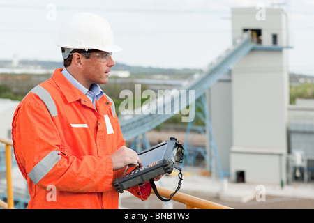 Engineer with handheld computer - Stock Photo