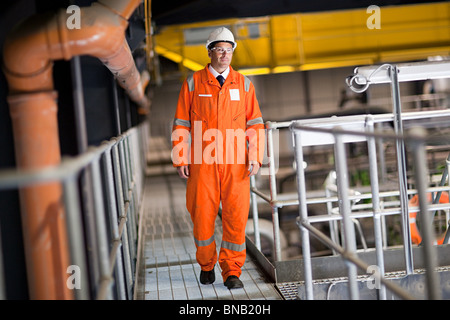 Engineer walking along walkway in factory - Stock Photo