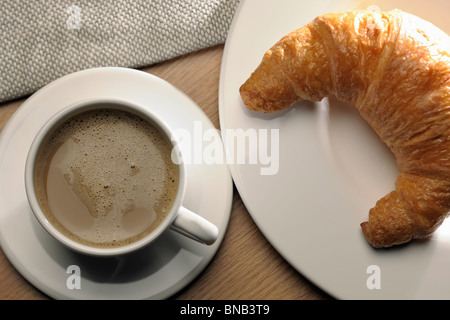 A white cup filled with black coffee and a croissant on a white plate. The coffee and croissant is typically a French - Stock Photo