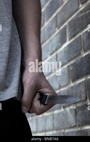 Hand of a young male holding a knife walking past a brick wall - Stock Photo