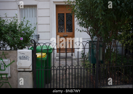 Apartment Building Front Door paris, france, plastic wheely trash bins in front of apartment