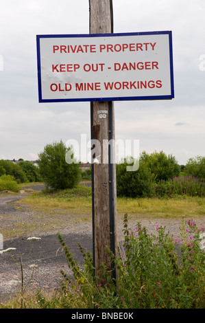 PRIVATE PROPERTY KEEP OUT DANGER OLD MINE WORKINGS sign on former colliery site at The British Torfaen South Wales - Stock Photo