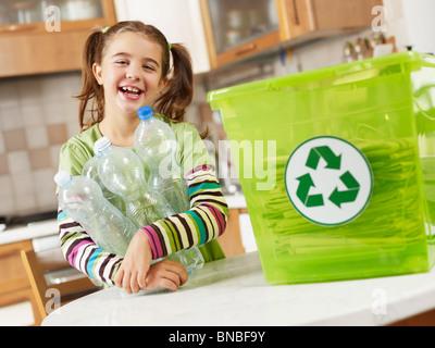 Girl holding plastic bottles for recycling - Stock Photo