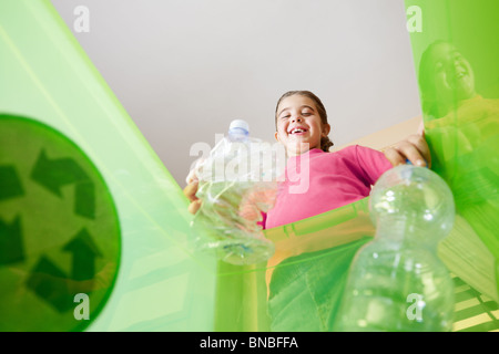 Girl holding plastic bottles for recycling, viewed from inside recycling bin. Copy space - Stock Photo