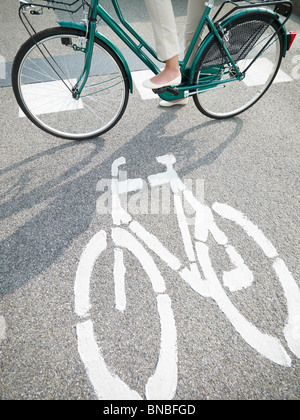 cropped view of female commuter on bike - Stock Photo