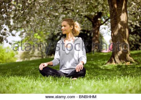 A mid adult woman sitting cross-legged under a tree - Stock Photo