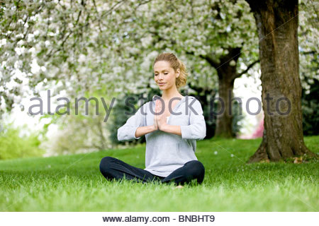A mid adult woman meditating in the park - Stock Photo