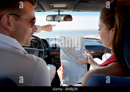 Couple looking at map in car by sea - Stock Photo