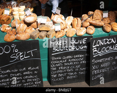 A variety of bread on display for sale on a stall at Borough Market in London - Stock Photo