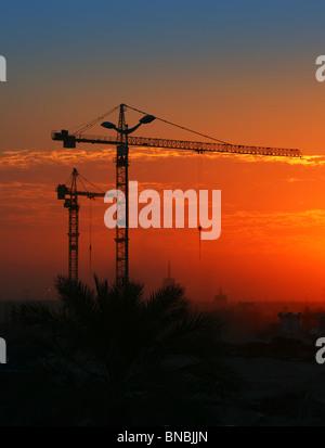 Construction crane over orange sunset sky - Stock Photo