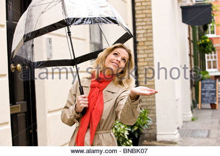 A mid adult woman holding an umbrella, checking for rain - Stock Photo