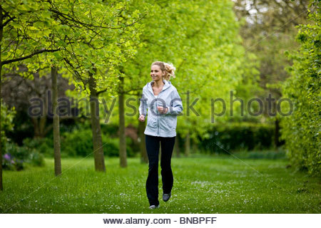 A mid adult woman jogging in the park - Stock Photo
