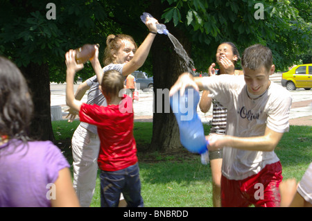 Hot summer day children play with water. - Stock Photo