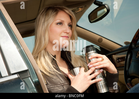 blonde woman sitting in parked car drinking tea thermos flask - Stock Photo