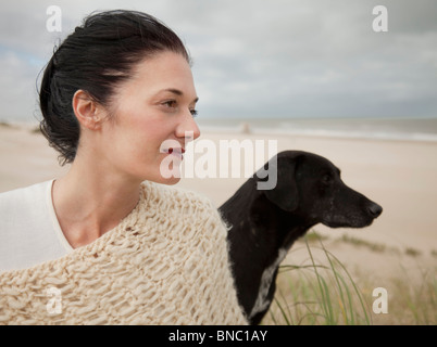 Woman with dog looking out to the ocean - Stock Photo