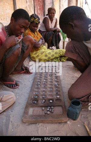 Mozambicans playing traditional board game in the street, Ilha de Mozambique. - Stock Photo