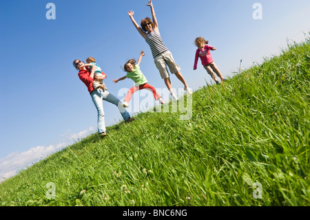 Family playing with joy on a grassy hill in Trentino, Italy. - Stock Photo