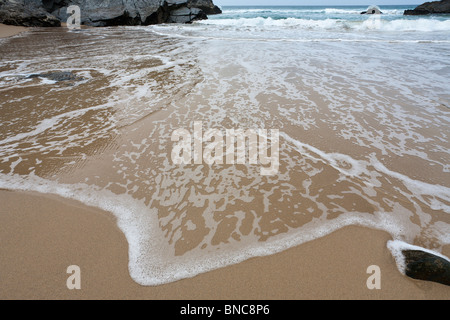 Waveforms at Bedruthan Beach. A wave flows smoothly over the flat sands of beach at Bedruthan Steps - Stock Photo